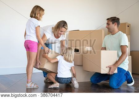 Mother, Father And Two Daughters With Cardboard Boxes In Living Room. Happy Young Family Relocating