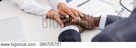 Partial View Of Doctor Touching Hands Of African American Man Near Clipboard And Pen On Desk, Horizo