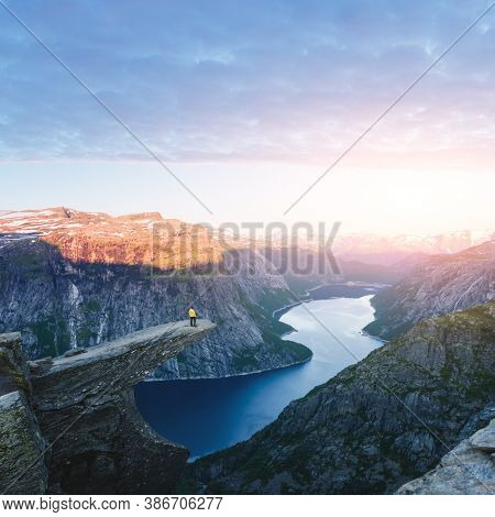 Tourist on Trolltunga rock in Norway mountains. Landscape photography