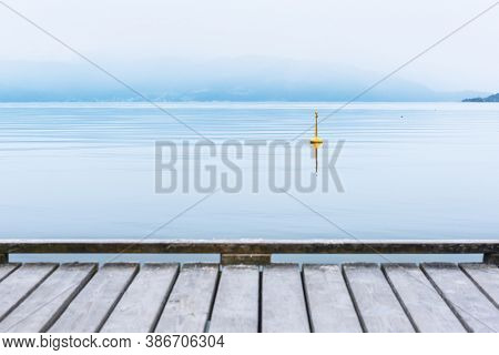 Misty morning on Norheimsund village. Wooden pier on hardangerfjord, Norway, Europe. Landscape photography