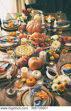 Thanksgiving dinner. Roasted turkey garnished with cranberries on a rustic style table decoraded with pumpkins, vegetables, pie, flowers and candles