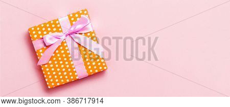 Wrapped Christmas Or Other Holiday Handmade Present In Paper With Pink Ribbon On Pink Background. Pr