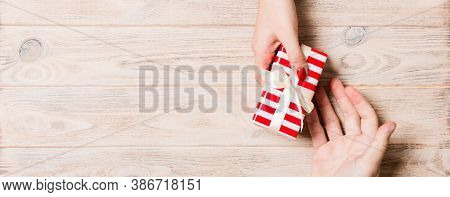 Top View Of Couple Giving And Receiving A Gift On Wooden Background. Romantic Concept With Copy Spac