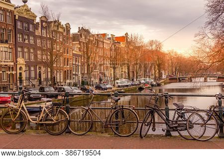 Amsterdam Canal And Bikes During A Sunset