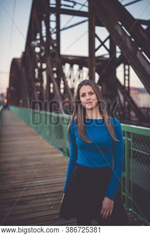 Beautiful Young Woman With Long Healthy Dark Blonde Hair In Blue Long Sleeve Shirt And Black Skirt O