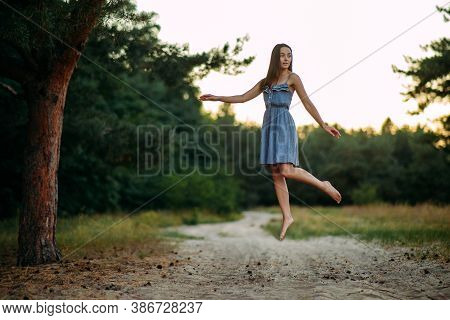 Young Woman Levitates In Pine Forest In The Air Above The Ground.