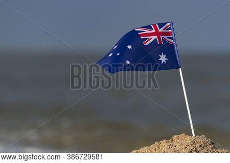 Flag Of Australia In Sand On The Beach. Seaside Holiday In Australia