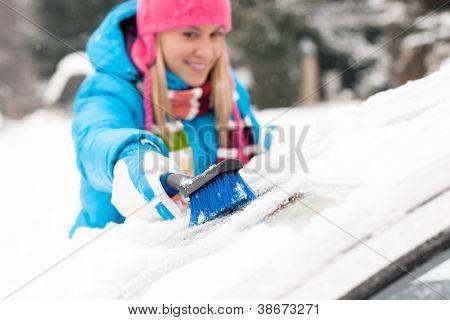 Woman wiping snow car window using brush winter happy work