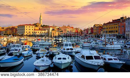 Rovinj, Istria, Croatia. Motorboats and boats on water in port Rovigno. Medieval vintage houses of old town. Yachts landing, high tower of Church of Saint Euphemia. Morning sunrise blue sky.