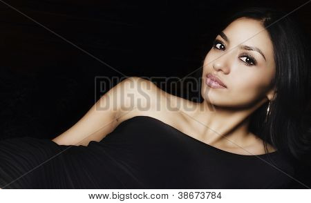 Portrait of a beautiful exotic young woman wearing black dress with gorgeous face.