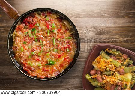 Braised Tomatoes With Onions In A Plate On A Brown Wooden Background. Stewed Tomatoes With Onions In
