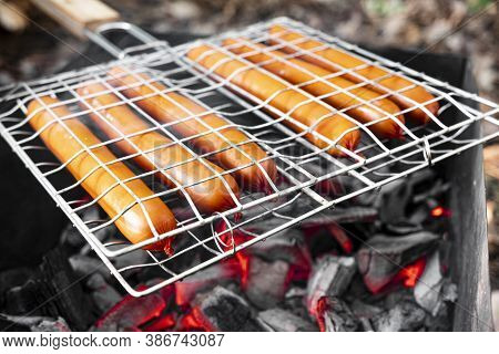 Grilled Sausages On Grill With Smoke And Flame On A Forest. Rustic Sausage At The Stake-sausages Are