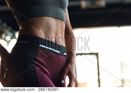 Perfect Shape. Cropped Shot Of Athletic Fitness Woman Showing Abs While Working Out At Gym