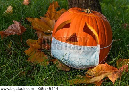 Halloween Pumpkin With Sad Eyes Wearing Mask, No Party During Covid Or Coronavirus Outbreak