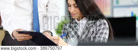 Portrait Of Businesswoman Signing Papers Sitting In Office. Attractive Young Woman Wearing Luxury Su