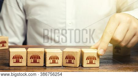Man Puts Blocks With Shop Symbols In A Row. Building A Successful Business Empire. Franchise Concept