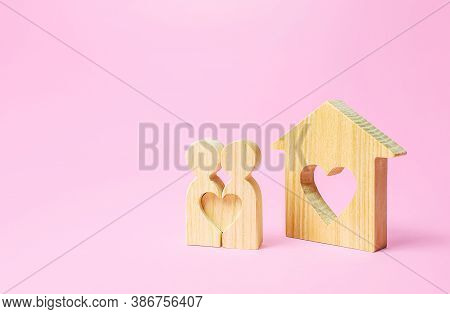 Figures Of A Love Couple Stand Near House With A Heart. Affordable Cheap Housing For Young Couples A