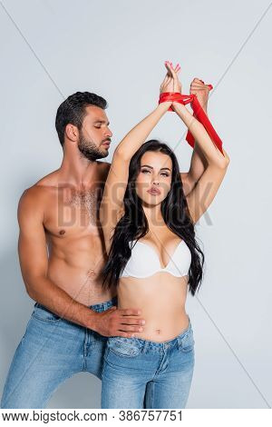 Submissive Woman With Tied Hands Near Dominant Man Isolated On White