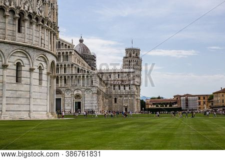 Pisa, Italy - July 9, 2017: View Of Tourists, San Giovanni Baptistery, Pisa Cathedral And Leaning To