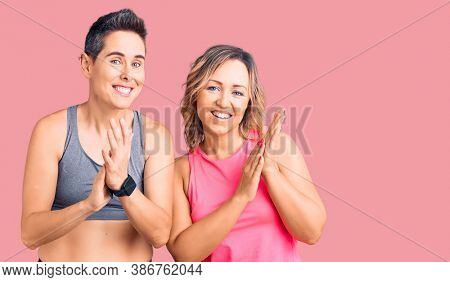 Couple of women wearing sportswear clapping and applauding happy and joyful, smiling proud hands together