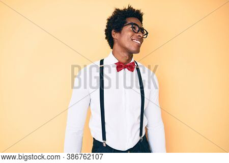 Handsome african american man with afro hair wearing hipster elegant look looking away to side with smile on face, natural expression. laughing confident.