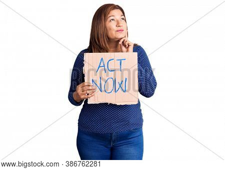 Middle age latin woman holding act now banner serious face thinking about question with hand on chin, thoughtful about confusing idea