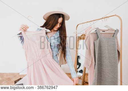 Stylish Caucasian Young Woman In Hat And Business Suit In Fashion Boutique While Shopping. High Qual