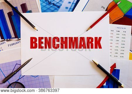 Benchmark Is Written In Red On Paper Next To Pencils, Graphs And Pens.