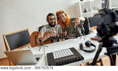 Man And Woman Showing Thumbs Up And Pointing Down, Asking For Subscription While Recording Video Blo