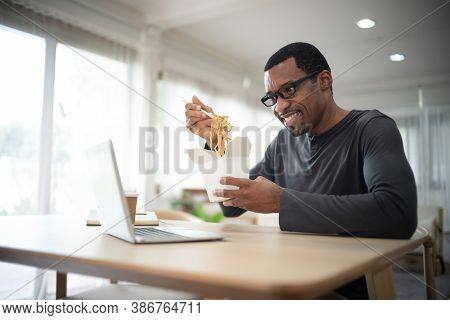 Handsome African American Freelancer Eating Takeaway Asian Food,spaghetti, With Chopsticks.he Online