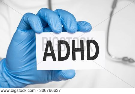 Doctor Holding A Card With Text Adhd Attention Deficit Hyperactivity Disorder, Medical Concept