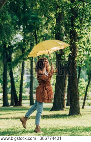 Side View Of Curly Woman In Raincoat And Jeans Holding Umbrella In Park