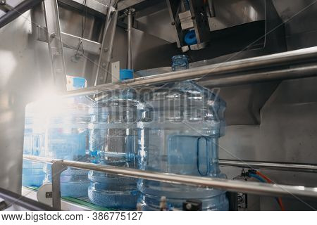Plastic Bottles Or Gallons On Automated Conveyor Production Line. Water Factory, Toned