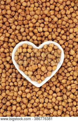 Healthy roasted chickpeas in a porcelain heart shaped bowl forming a background. Vegan & vegetarian health food high in fibre, protein, vitamins and minerals. Flat lay, top view.