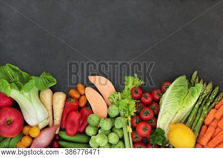 Organic fresh fruit & vegetables for a healthy diet high in antioxidants, anthocyanins, lycopene, carotenoids, minerals, vitamins, dietary fibre & smart carbs. Border on slate background. Top view.