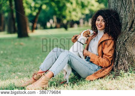 Selective Focus Of Young Woman In Raincoat Playing With Jack Russell Terrier And Looking At Camera N