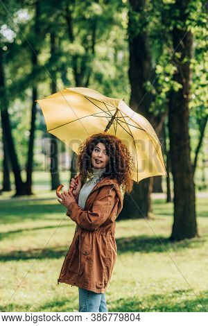 Young Woman In Raincoat Holding Umbrella In Park
