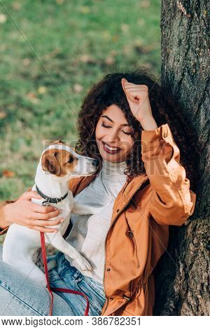 Curly Woman In Raincoat Holding Jack Russell Terrier Near Tree In Park