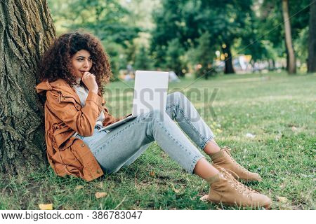 Selective Focus Of Thoughtful Woman In Raincoat Using Laptop On Grass Near Tree In Park