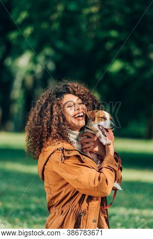Young Woman In Raincoat Hugging Jack Russell Terrier In Park