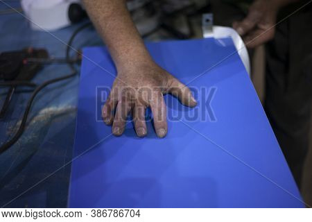 The Self-adhesive Advertising Film Is Cut With A Knife. Creation Of An Advertising Sign In A Worksho