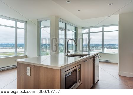 Modern, bright, clean empty kitchen interior with stainless steel appliances in a luxury house.