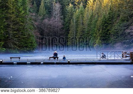A Family On A Winter Ice Fishing At Rice Lake In Lynn Canyon Park. Pier At Ice Covered Lake, Light F