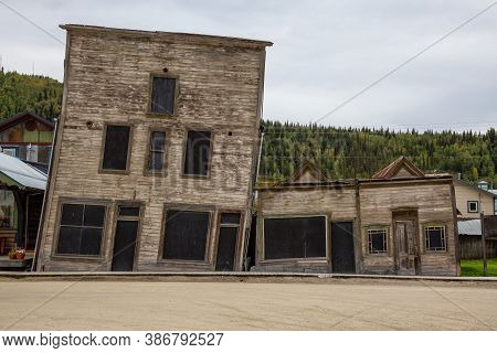 Exterior View Of An Old Broken And Slanted House In A Small Touristic Town, Dawson City, During A Su