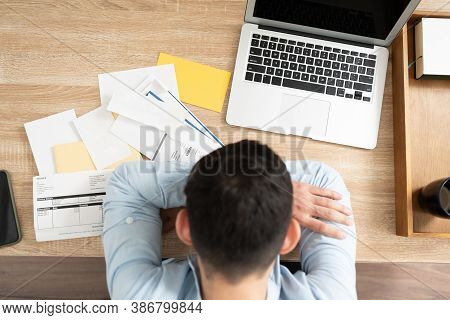 Top View Of A Broke Man With A Lot Of Debt Giving Up And Feeling Overwhelmed In Front Of Too Many Bi