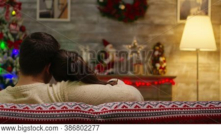 Back View Of Romantic Couple Sitting On Couch On Christmas Day With Xmas Tree In The Background. Xma
