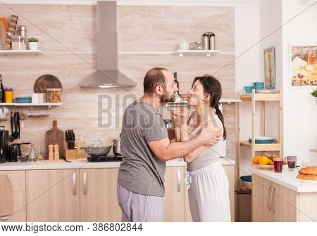 Husband And Wife Screaming In Frustration At Each Other During Breakfast In Kitchen. Domestic Violen