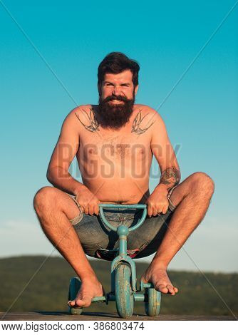Guy Riding Childs Tricycle. Funny Man On A Bicycle. Emotional Crazy Guy On A Childrens Bike