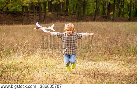 Happy Child Playing Outdoors. Happy Boy Play Airplane. Little Boy With Plane. Little Kid Dreams Of B