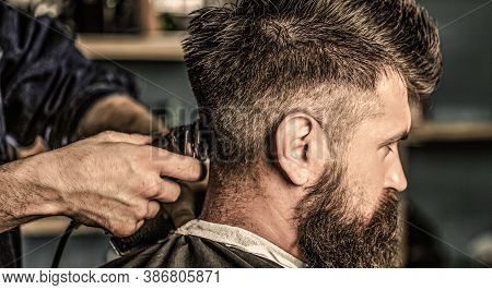 Haircut Concept. Man Visiting Hairstylist In Barbershop. Barber Works With Hair Clipper. Hipster Cli